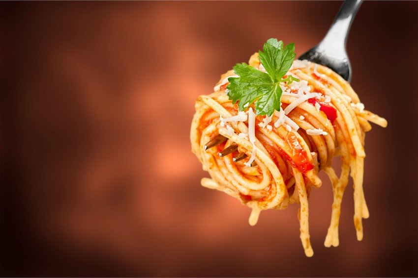 Photo of spaghetti and red sauce curled around a fork