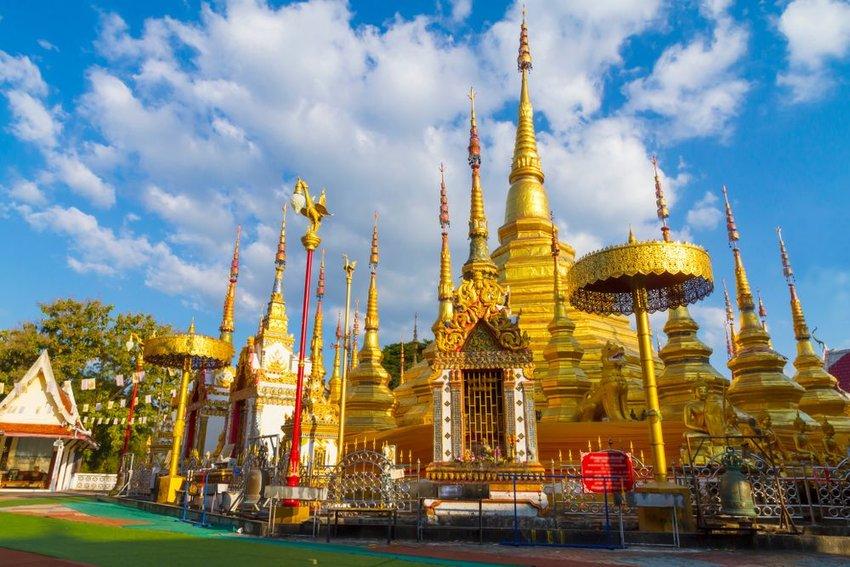 Tourist photo of golden pagoda in Thailand under blue skies