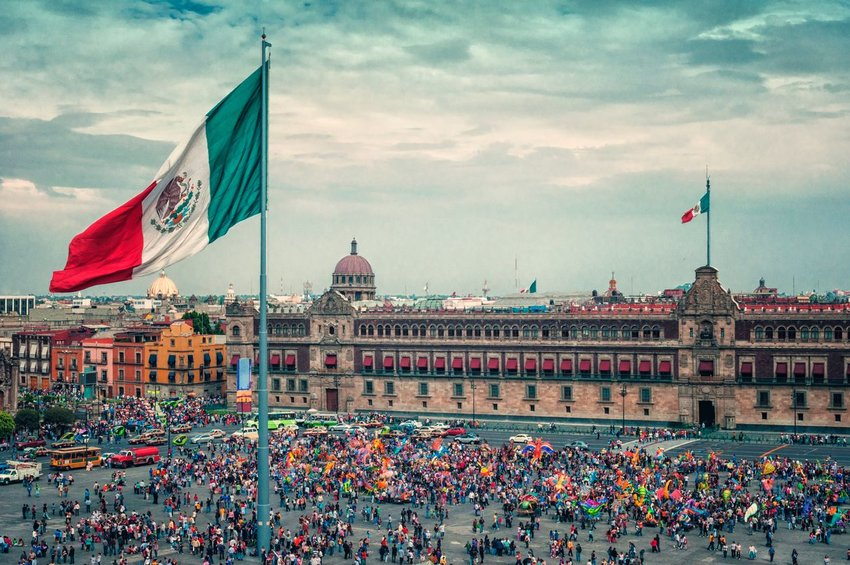 Crowd of people standing in Zocalo Square, Mexico City, with Mexican flags waving