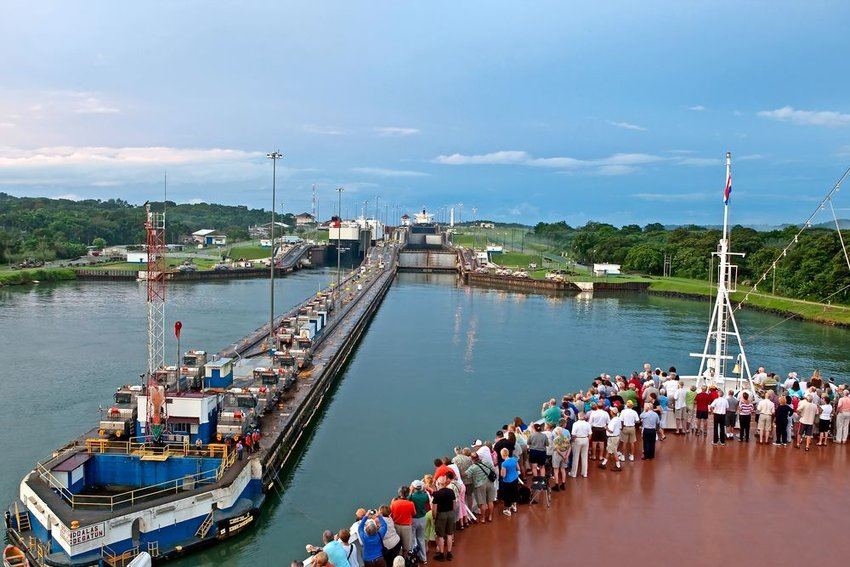 Crowd of tourists watch as a ship enters the Panama Canal