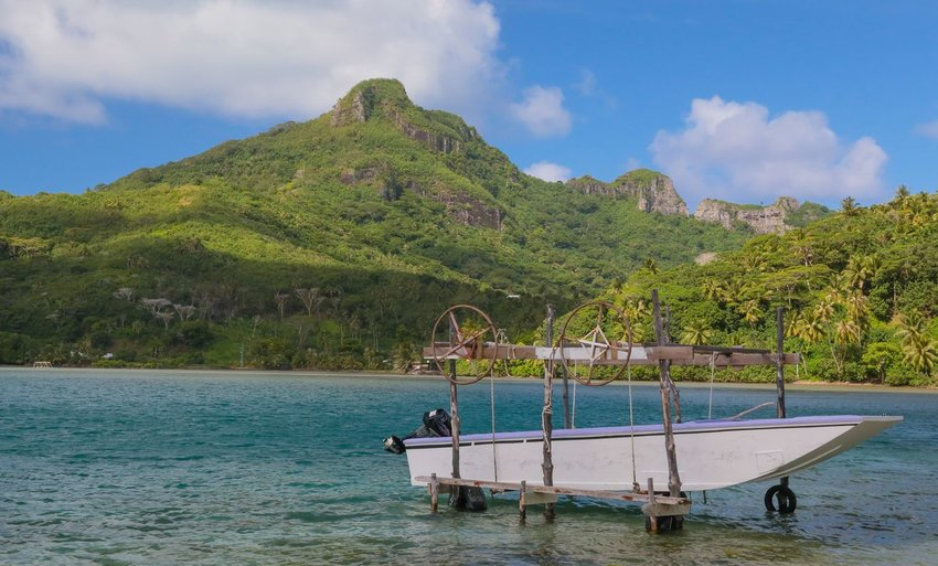 Photo of a small fishing boat on the water in front of a tropical mountain landscape