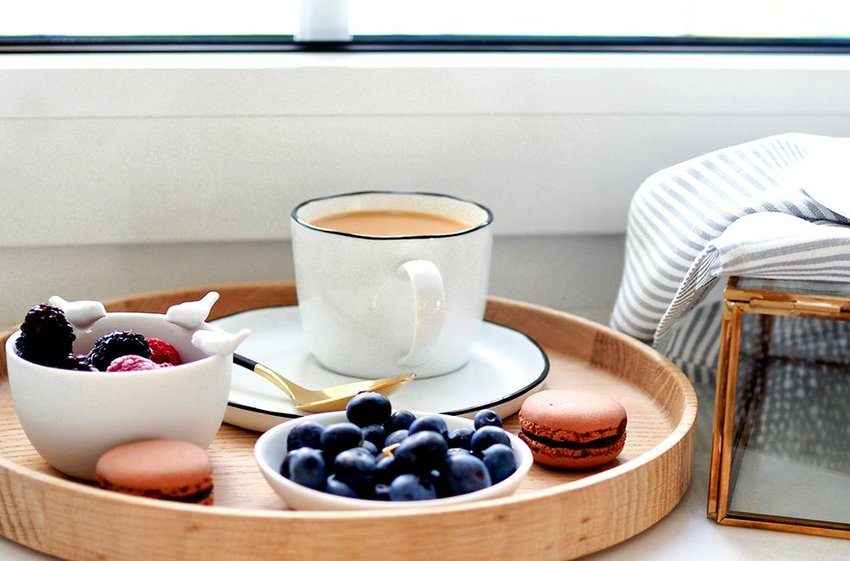 Photo of a tray holding a cup of coffee, macarons, and fruit