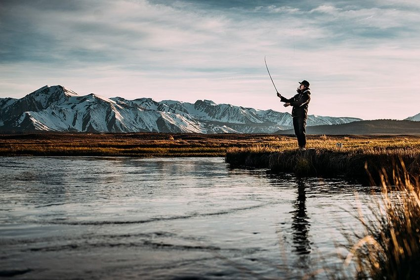 Photo of a man fishing on the banks of a river with mountains in the background