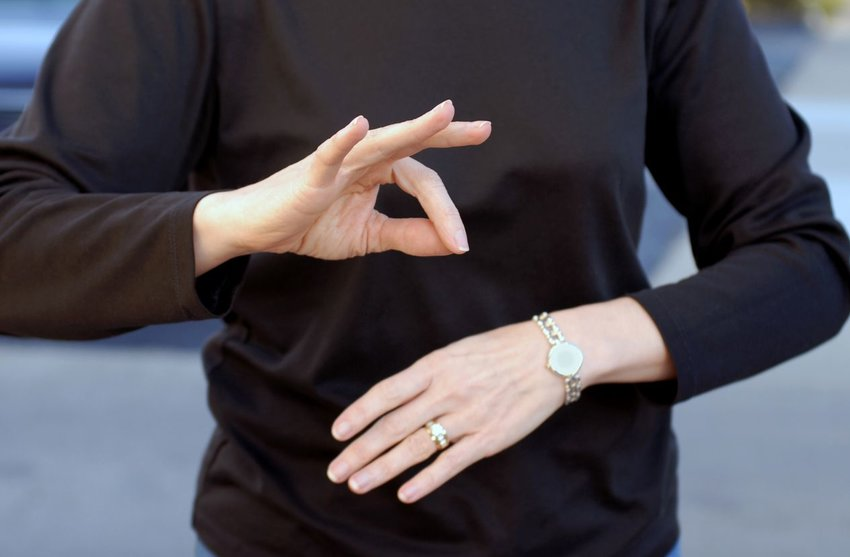 Up close view of woman using both hands to perform sign language message