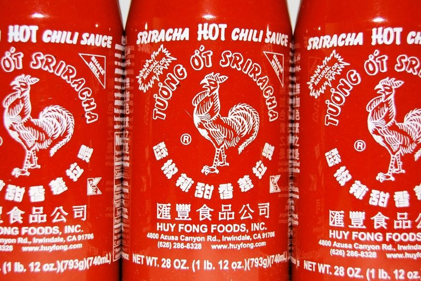 Up close view of sriracha bottles with iconic rooster logo from Huy Fong Foods