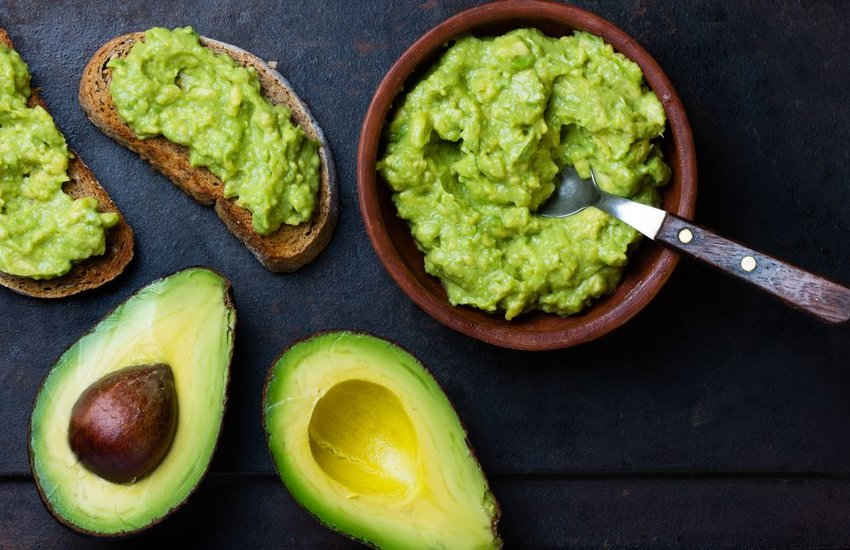Fresh avocado mashed up into guacamole and served over toast against dark background
