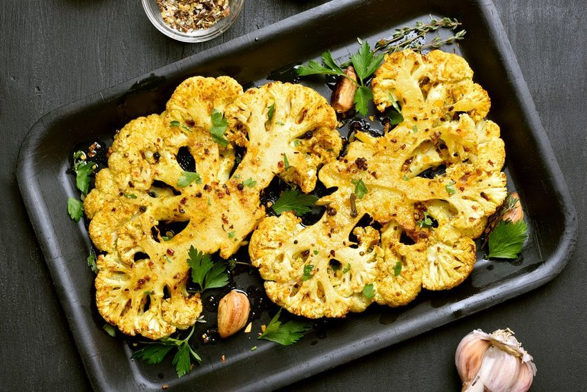 Sliced cauliflower seasoned and oven baked in a deep metal pan