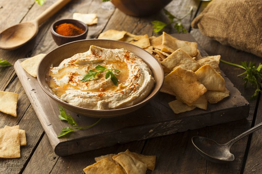 Bowl of traditional hummus with oil and sliced pita bread, served on rustic wooden table