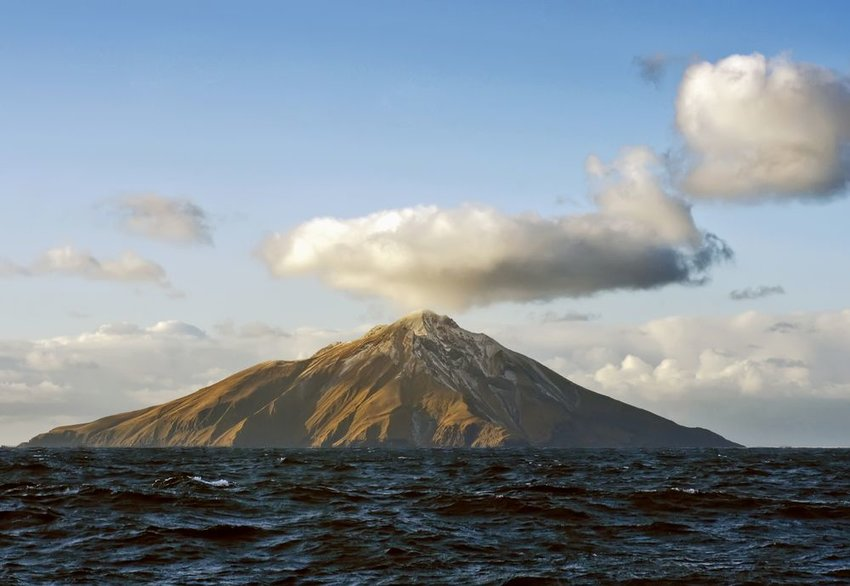 Solitary volcano in the Aleutian Island mountain range with choppy waters and cloudy skies, Alaska