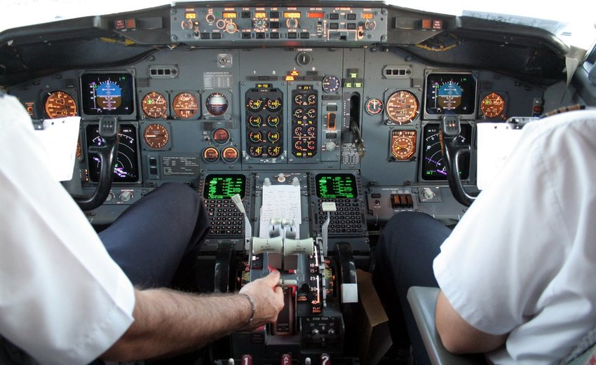 Interior view of cockpit with pilot and copilot managing electronic controls