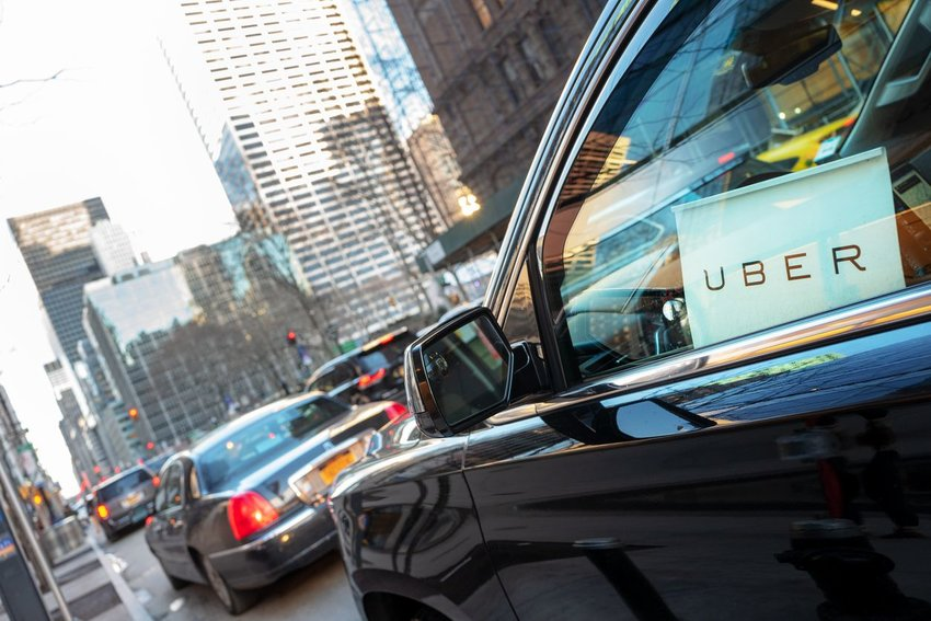 Cars sitting in traffic with rideshare Uber sign placed in driver's side window