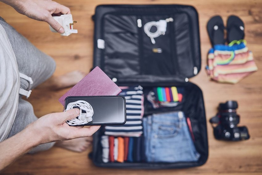 Person opening luggage and holding charging devices for smartphone
