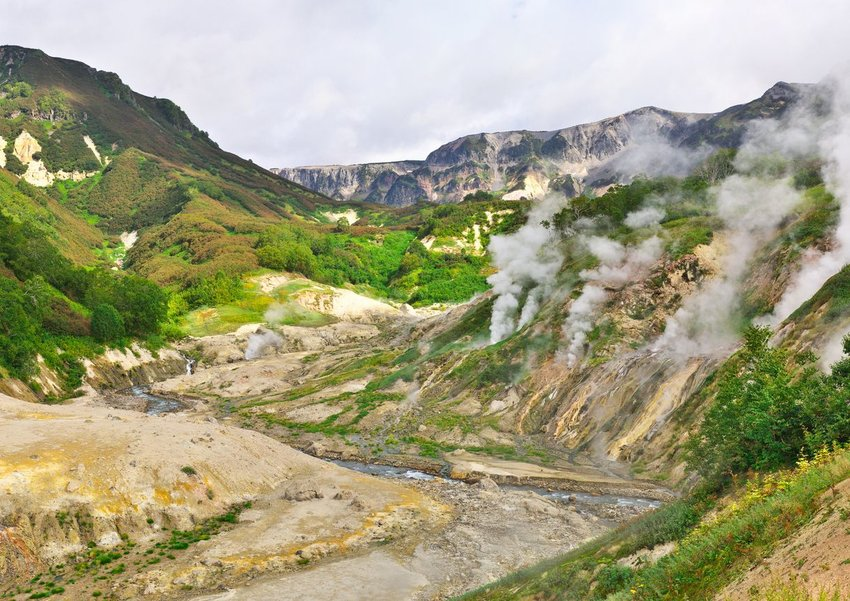 Iconic Valley of Geysers with steam rolling off rocky hills in Kamchatka, Russia