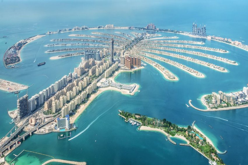 Aerial view of Dubai Palm Jumeirah island with skyscrapers and blue waters