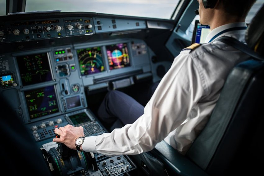 Cockpit view of pilot with hand on controls guiding plane in flight