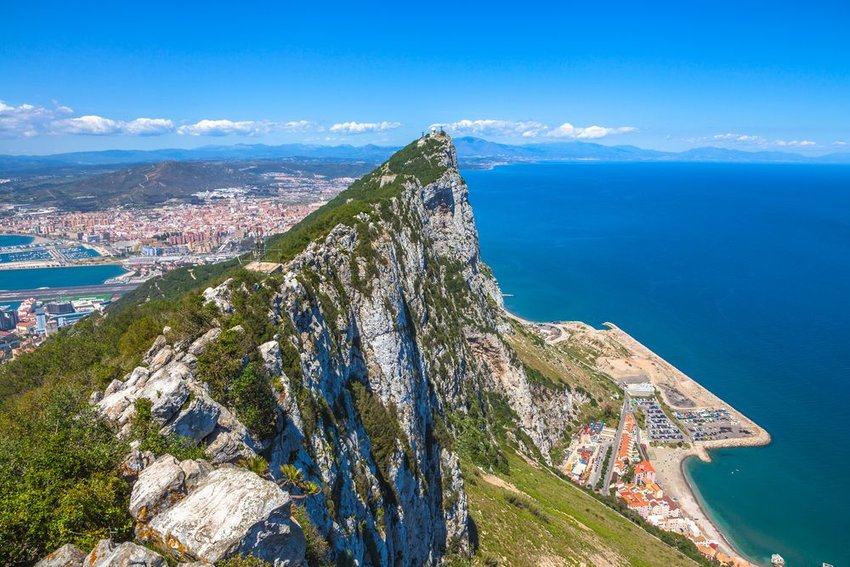 Aerial view of Rock of Gibraltar with rocky peak against distant city and ocean