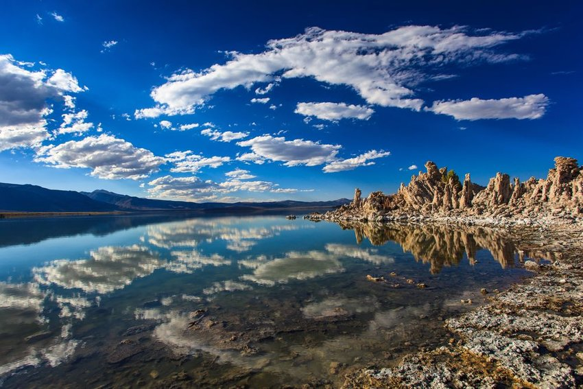 Glassy water reflects clouds with rocky tufa towers in background at Mono Lake, California