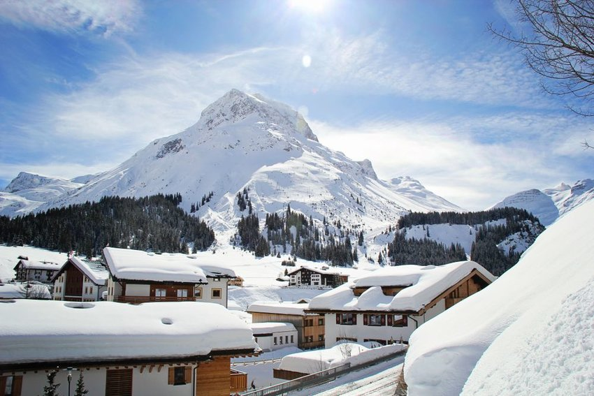 Brightly lit ski resort town adjacent to a snowy mountain, Lech, Austria