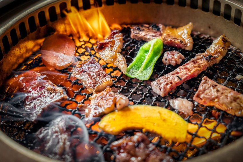 Assorted meats and vegetables cooking on a Korean barbecue grill