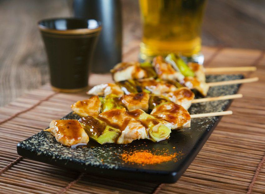Tray of elaborate Japanese yakitori skewers with meat and vegetables, served on black marble