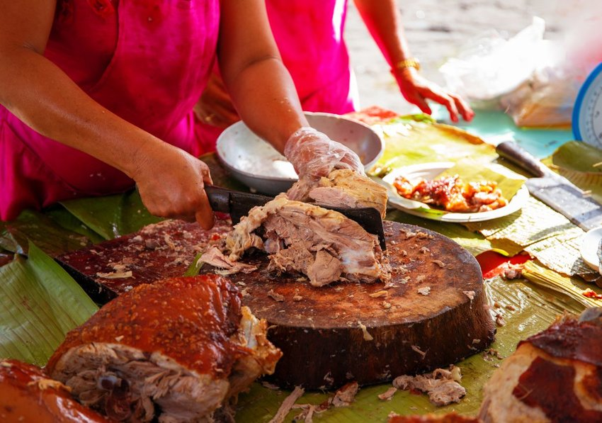 Women preparing cooked Filipino lechón barbecue, cutting meat on wooden board