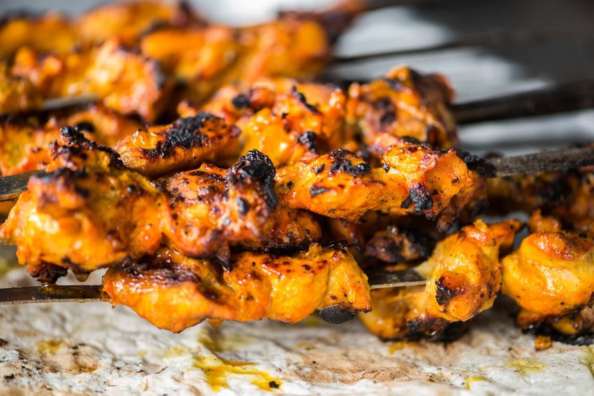 Up close view of traditional tandoori chicken skewers grilled with char marks