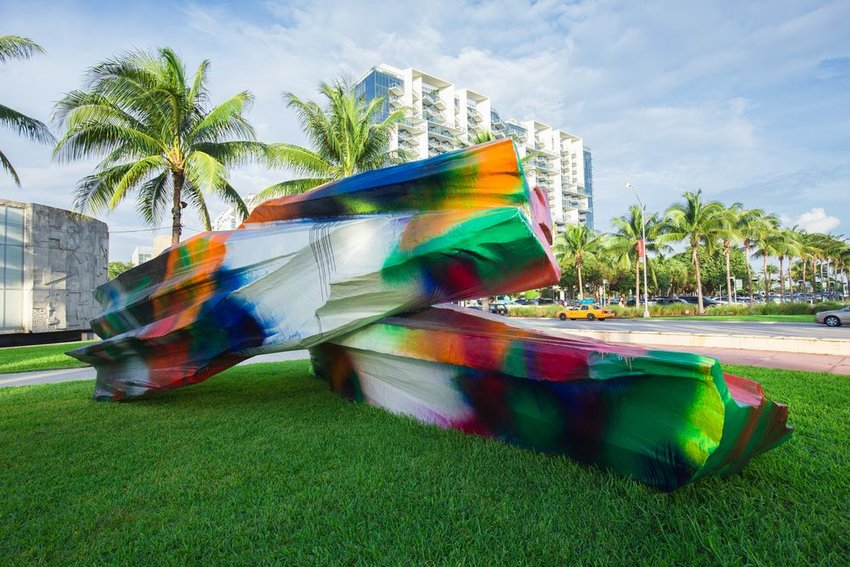 Outdoor art exhibit showing large, multicolored sculptures on grass with Miami, Florida trees in background