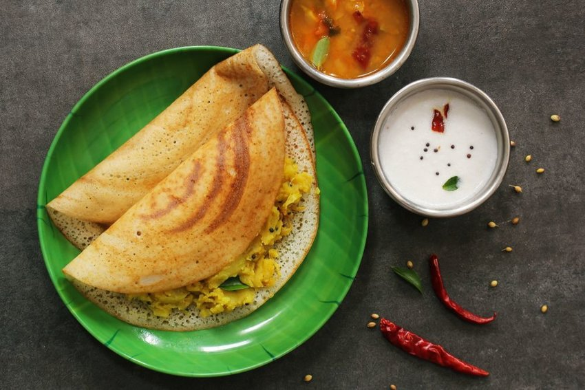 Two dosas on green plate filled with chutney and served with dips and red peppers