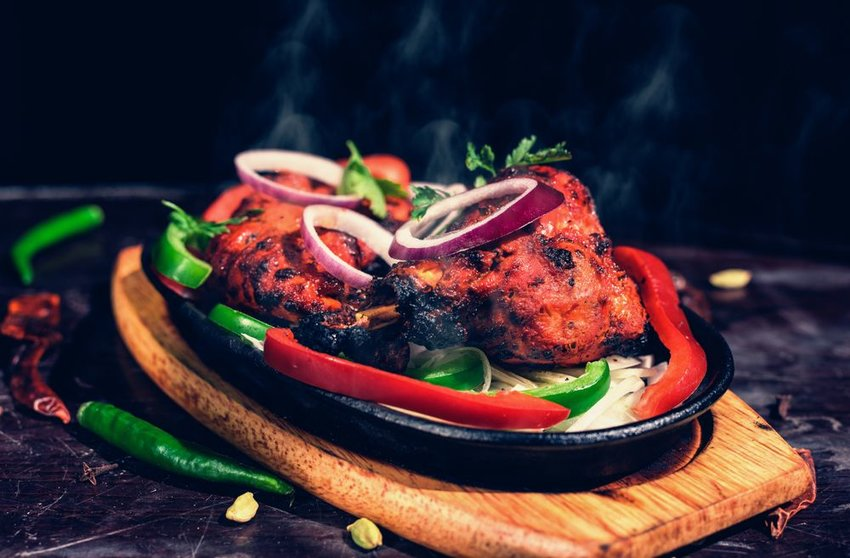 Meat and vegetables roasted in tandoor, served with peppers on a wooden plank