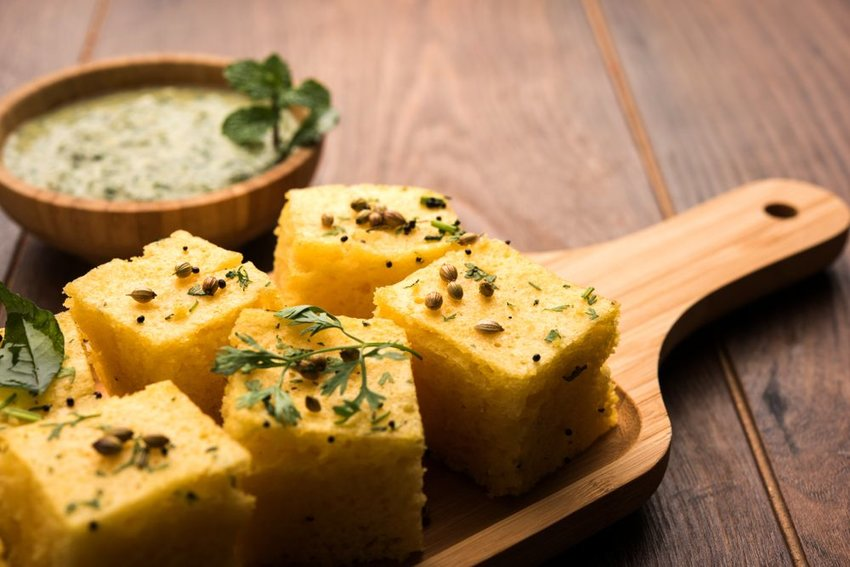 Up close view of traditional Indian dhokla cubes with seeds and garnishes
