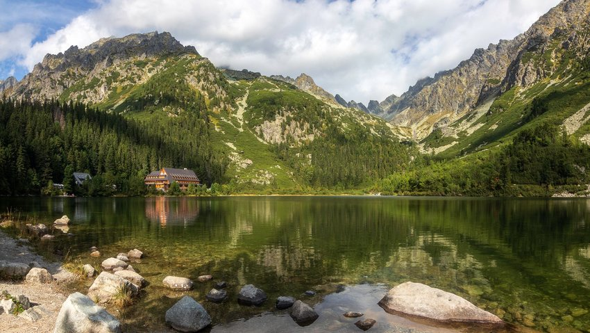 Popradske Lake seen during the day, with tall foresty mountains and green waters, Tatras