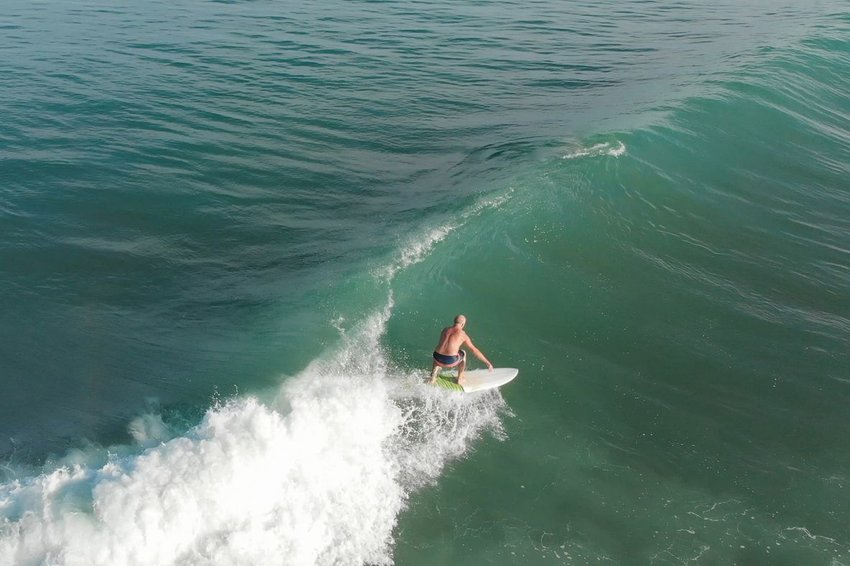 Older man surfing a white wave in Costa Rican waters