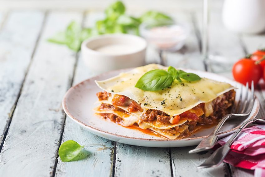 Lasagna with silverware on blue wood table