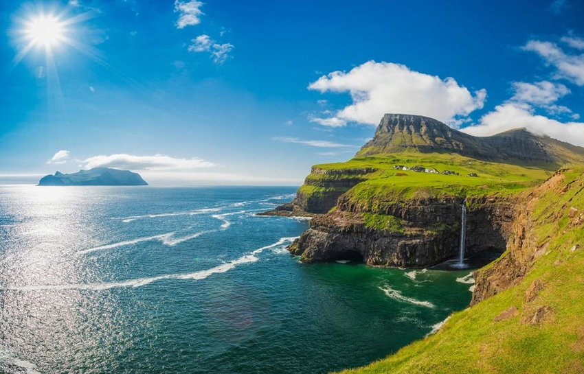 Waterfall into the ocean off of Faroe Islands in Denmark