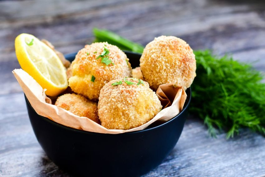 Arancini in a black bowl with a lemon slice