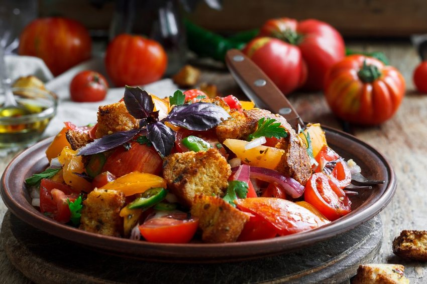 Panzanella in a bowl with fresh tomatoes in the background