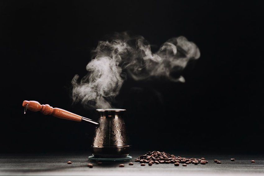 Turkish coffee serving pot with steam rising in air and coffee beans scattered on ground