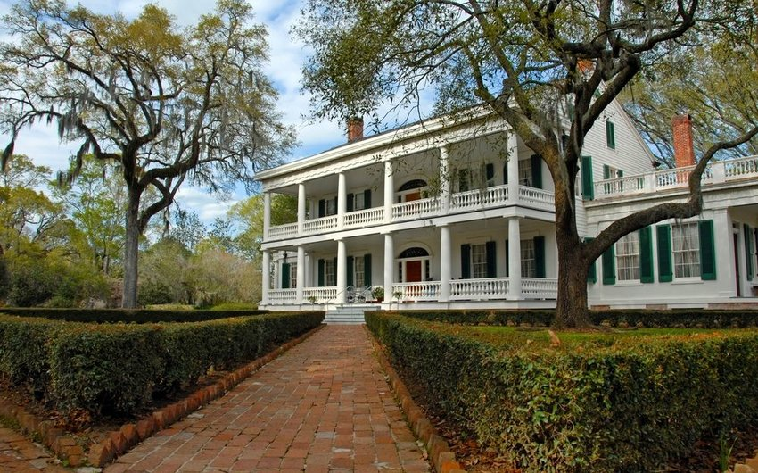 Old southern farm house with curated shrubs and trees
