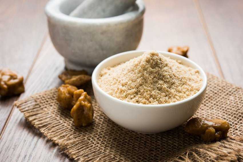 Ground up asafetida sprinkled into a white bowl with whole spices on table