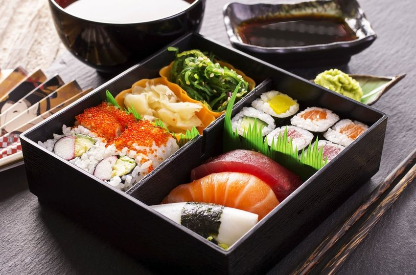 Traditional Japanese bento box filled with sushi, fish, and vegetables