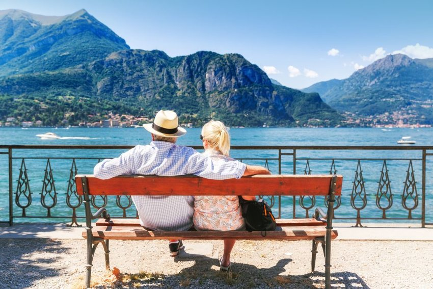 Man and woman resting on a bench overlooking the landscape in the middle of the day