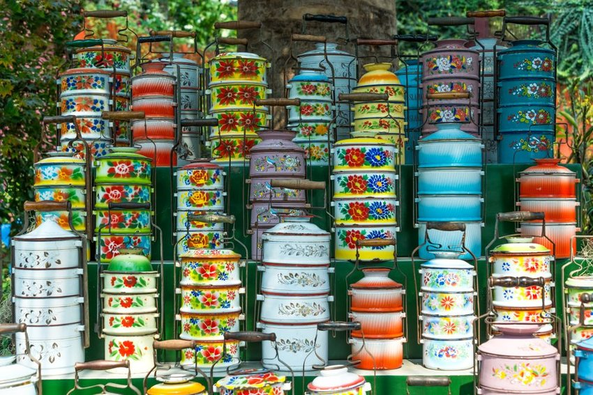 Traditional Indian tiffins of different colors stacked neatly in columns