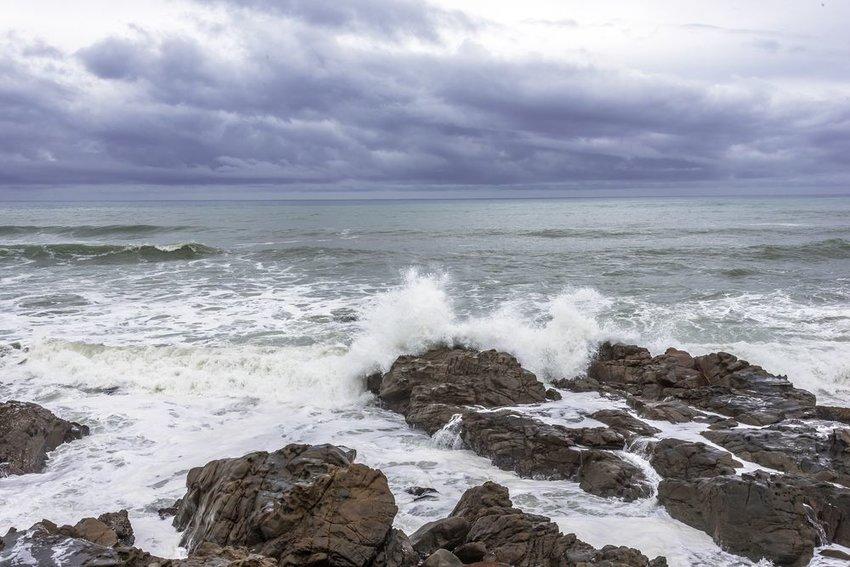 Cloudy skies and crashing ocean waves smashing rocks