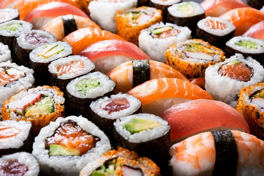 Rows of classic sushi rolls, showing rice, fish, and iconic circular sushi shapes