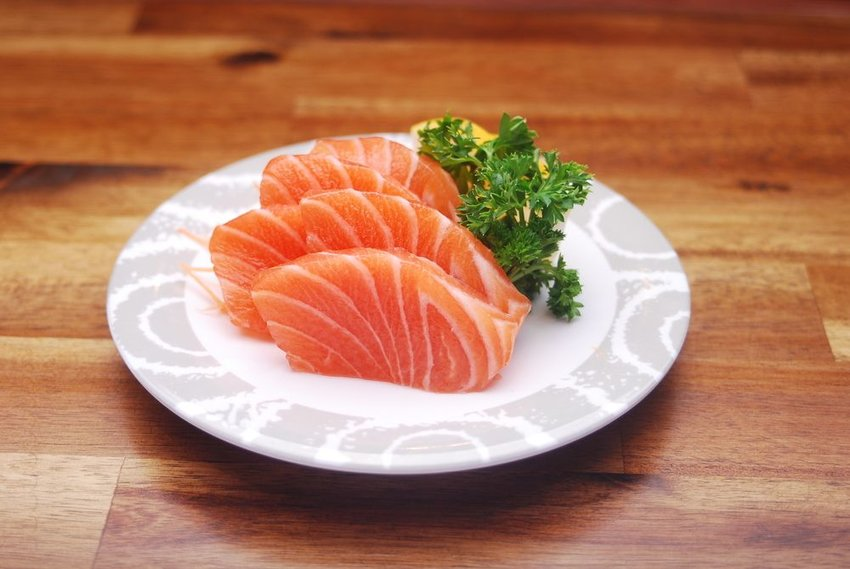 Plate of simple, traditional sashimi slices, showing fish and green garnish on white plate