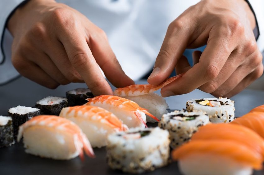 Up close view of sushi chef's hands placing fish on rice, preparing sushi rolls