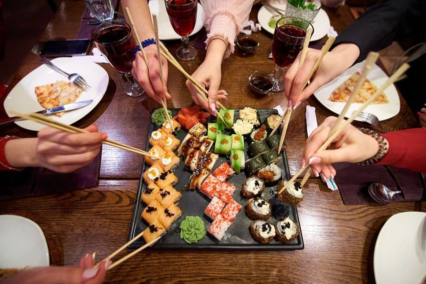 Group of people sitting around a sushi plate, using chopsticks to take sushi rolls