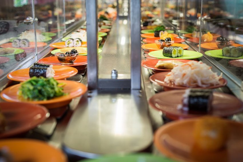 Iconic conveyor belt sushi restaurant, showing different types of sushi rolls on colored plates