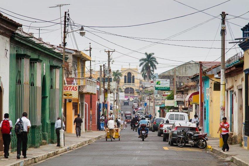 Street view of locals and vehicles in Santa Ana, El Salvador