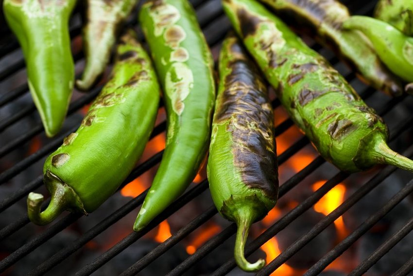 Up close view of green peppers roasting and charring over a grill's open flames